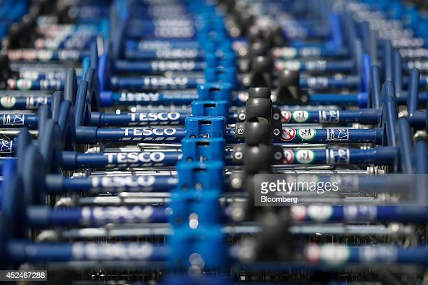 Tesco logos sit on the handles of shopping carts stored outside a Tesco Extra Supermarket operated by Tesco Plc in London UK on Tuesday July 1 2014...
