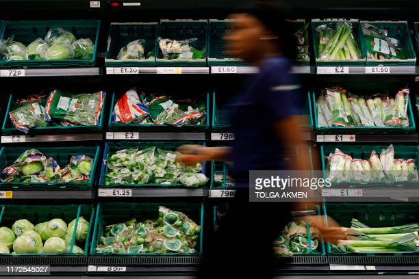 A Tesco staff member walks past a display of fresh vegetables at a Tesco Superstore in south London on September 30 2019 Tesco Britain's biggest food...