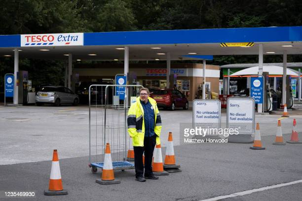 Tesco worker stands at the entrance to a Tesco Extra fuel station which has run out of diesel and unleaded fuel on September 24, 2021 in Cardiff,...