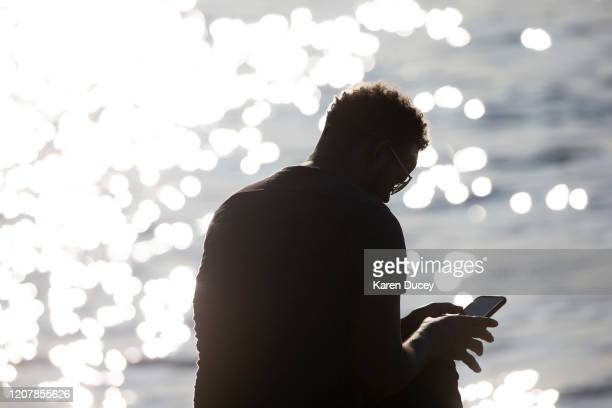 Tesfaldet Tekle sits quietly with his phone at Alki Beach Park on March 20 2020 in Seattle Washington Tekle is a driver for Uber and Lyft and says...