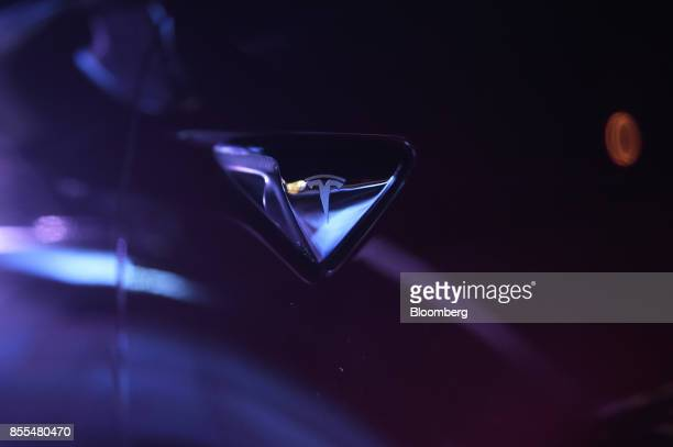 A Tesla badge sits on the body of a Tesla Motors Inc Model S electric automobile during an event at the Hornsdale wind farm operated by Neoen SAS...