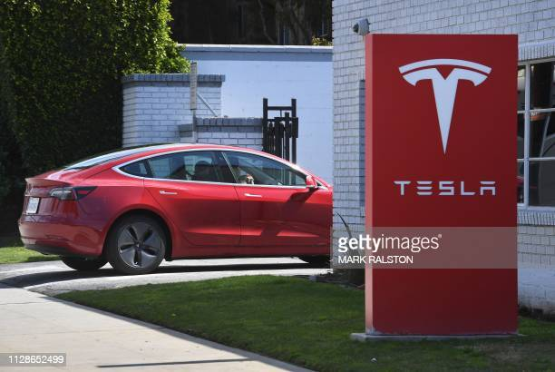 A Tesla car arrives at a service center after the company indicated it would be closing showrooms and in the future selling its cars online in Los...