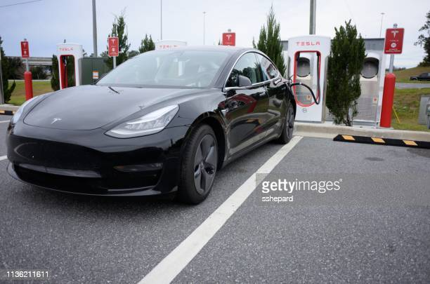 tesla car at supercharger station along interstate - supercharged engine stock pictures, royalty-free photos & images