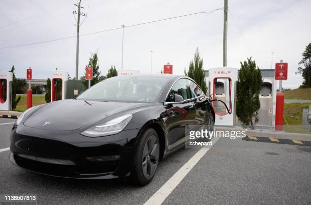 tesla car at supercharger station near interstate - supercharged engine stock pictures, royalty-free photos & images