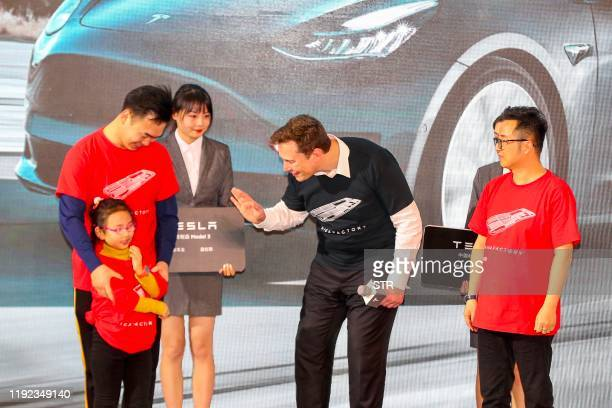 Tesla CEO Elon Musk chats with a child during the Tesla Chinamade Model 3 Delivery Ceremony in Shanghai Tesla CEO Elon Musk presented the first batch...
