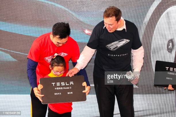 Tesla CEO Elon Musk gives a plaque to a child as buyers receive new cars during the Tesla Chinamade Model 3 Delivery Ceremony in Shanghai Tesla CEO...