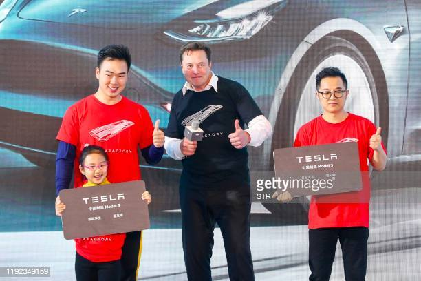 Tesla CEO Elon Musk poses for photos with buyers during the Tesla Chinamade Model 3 Delivery Ceremony in Shanghai Tesla CEO Elon Musk presented the...