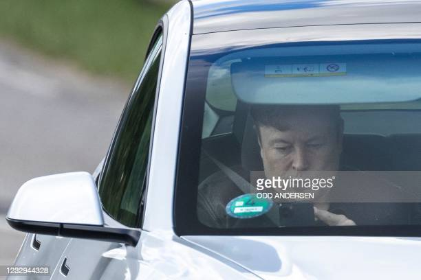"""Tesla CEO Elon Musk uses his mobile device as he sits in the car arriving to the construction site for the new plant, the so-called """"Giga Factory"""",..."""