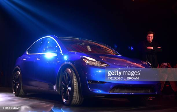 Tesla CEO Elon Musk walks beside the new Tesla Model Y at its unveiling in Hawthorne California on March 14 2019 Tesla introduced a new electric...