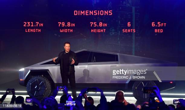 Tesla cofounder and CEO Elon Musk discusses vehicle dimensions in front of the newly unveiled allelectric batterypowered Tesla Cybertruck at Tesla...