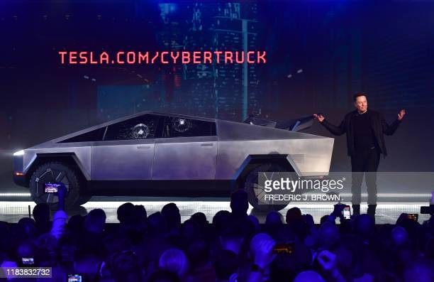 Tesla cofounder and CEO Elon Musk speaks in front of the newly unveiled allelectric batterypowered Tesla's Cybertruck with shattered windows after a...