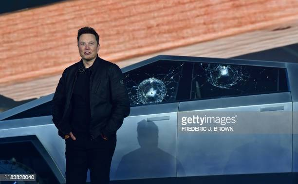 Tesla cofounder and CEO Elon Musk stands in front of the shattered windows of the newly unveiled allelectric batterypowered Tesla's Cybertruck at...
