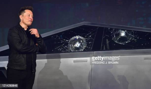 Tesla co-founder and CEO Elon Musk verbally reacts in front of the newly unveiled all-electric battery-powered Tesla Cybertruck with broken glass on...