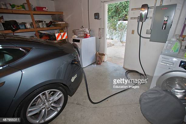 Tesla electric car recharging in garage in Green home that is off the grid Solar power and a rainwater harvesting system supply all the energy and...
