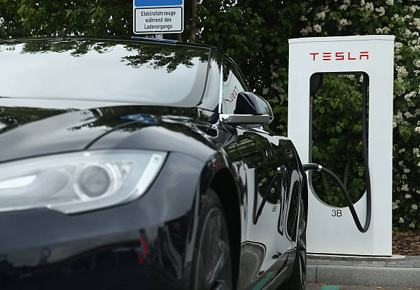 Tesla electric-powered sedan stands at a Tesla charging staiton at a highway reststop along the A7 highway on June 11, 2015 near Rieden, Germany....