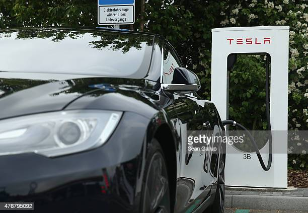 Tesla electricpowered sedan stands at a Tesla charging staiton at a highway reststop along the A7 highway on June 11 2015 near Rieden Germany Tesla...