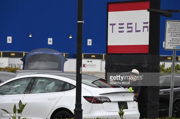 A Tesla employee cleans a car outside a Tesla showroom in Burbank California March 24 2020 Luxury electric car maker Tesla ended up closing its...