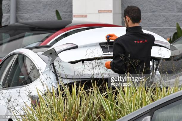 A Tesla employee works on a license plate frame outside a Tesla showroom in Burbank California March 24 2020 Luxury electric car maker Tesla ended up...