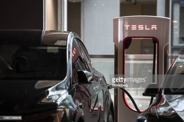Tesla Inc electric vehicles sit charging at a Supercharger station inside a parking lot in Hong Kong China on Friday Nov 23 2018 Teslais beefing up...