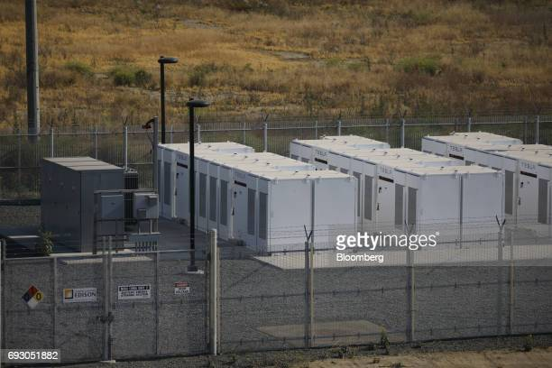 Tesla Inc Powerpacks and inverters stand behind a fence at the Southern California Edison Co Mira Loma energy storage system facility in Ontario...