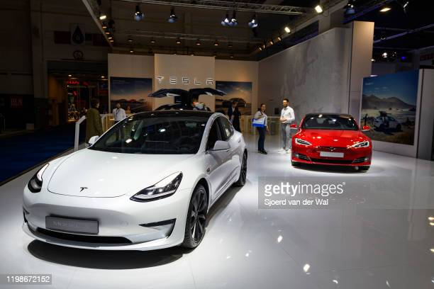 Tesla Model 3 compact sedan car in white with a Tesla Model S dual motor all electric sedan in red on display at Brussels Expo on JANUARY 09 2020 in...