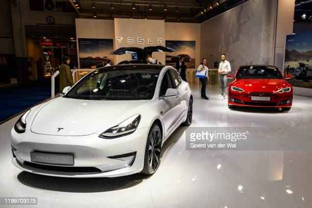 Tesla Model 3 compact sedan car in white with a Tesla Model S dual motor all electric sedan on display at Brussels Expo on January 9 2020 in Brussels...