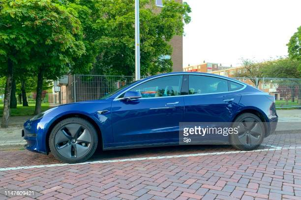 Tesla Model 3 electric car in blue parked on the street