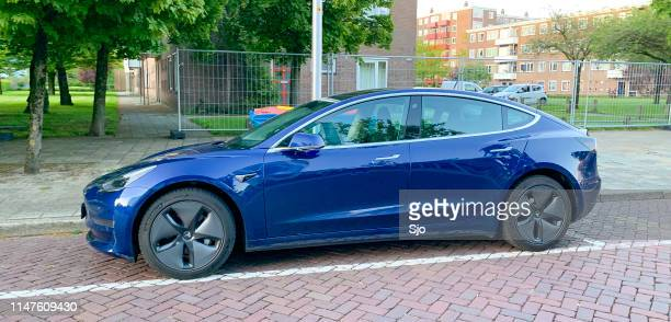 tesla model 3 electric car in blue parked on the street - tesla model 3 stock pictures, royalty-free photos & images