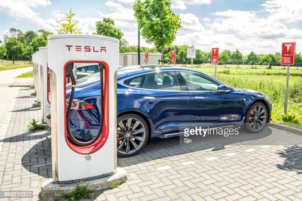 tesla modelo do carro elétrico em uma estação de carga supercharger - gratis - fotografias e filmes do acervo