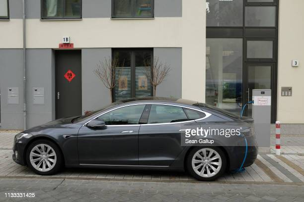 Tesla Model S electric car charges at a public charging column on March 2 2019 in Berlin Germany Tesla recently announced it is closing many of its...