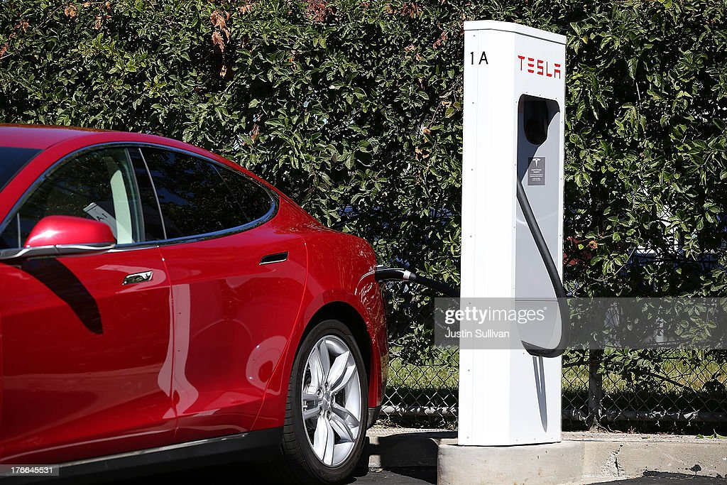 a tesla model s sedan is seen plugged into a new tesla. Black Bedroom Furniture Sets. Home Design Ideas