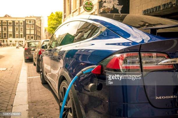 tesla model x charging on the street in amsterdam - 2018 stock pictures, royalty-free photos & images
