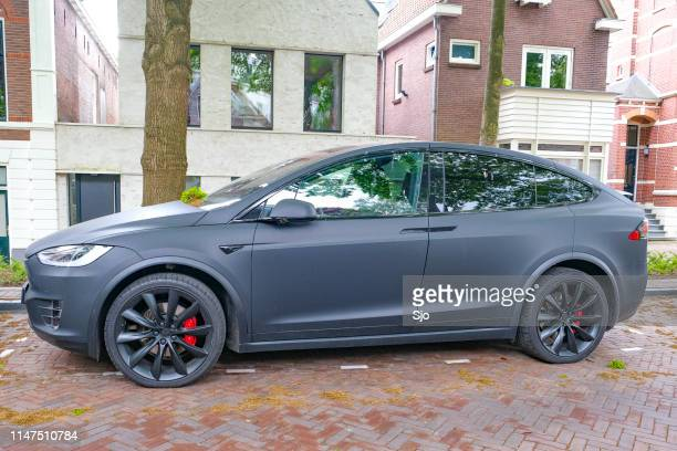 Tesla Model X electric SUV in matte black parked on the street