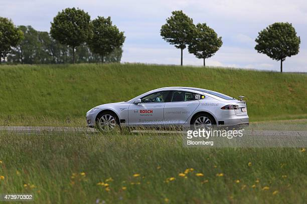 A Tesla Motors Inc Model S electric automobile fitted with Robert Bosch GmbH automated driving technology drives on a test track in Boxberg Germany...