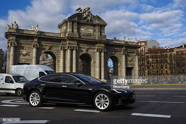 A Tesla Motors Inc Model S electric automobile operated Uber Technologies Inc drives past the Puerta de Alcala in Plaza de la Independencia in Madrid...