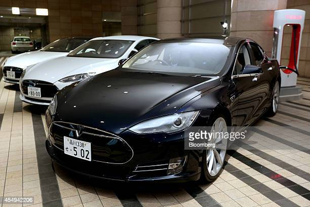 A Tesla Motors Inc Model S electric sedan stands on charge at a valet parking lot outside a hotel following a news conference in Tokyo Japan on...