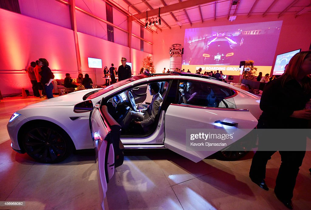 Tesla owners look at the new interior of a Tesla 'D' model electric sedan after Elon Musk, CEO of Tesla, unveiled the dual engine chassis, a faster and all-wheel-drive version of the Model S electric sedan, at the Hawthorne Airport October 09, 2014 in Hawthorne, California. The D will be able to accelerate to 60 miles per hour in just over 3 seconds.