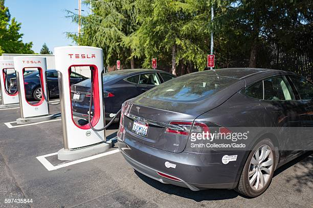 Tesla vehicles plugged in and charging at a Supercharger rapid battery charging station for the electric vehicle company Tesla Motors in the Silicon...