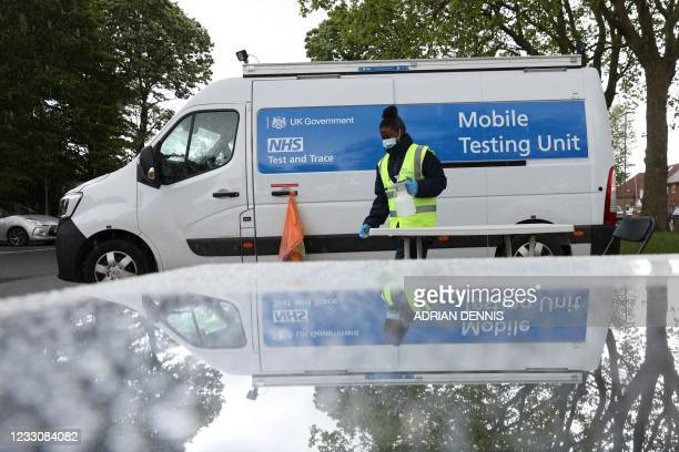 Test and Trace employee is reflected in a mirror as they clean down a table at a mobile coronavirus testing unit in Hayes, Hillingdon, west London on...