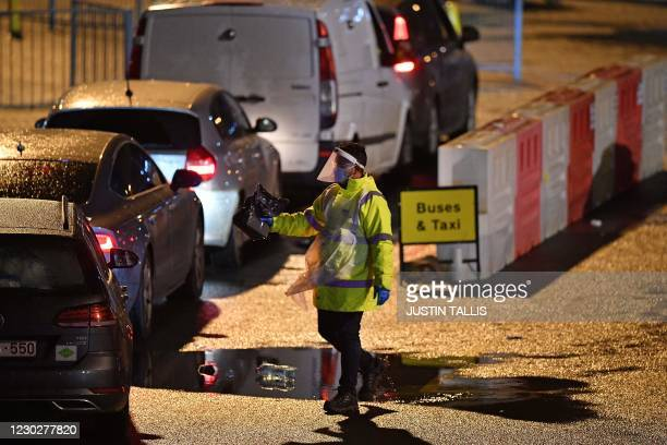 Test and Trace worker wearing PPE is seen beside car queuing at the Port of Dover, in Dover in Kent, south east England, on December 23 as the...