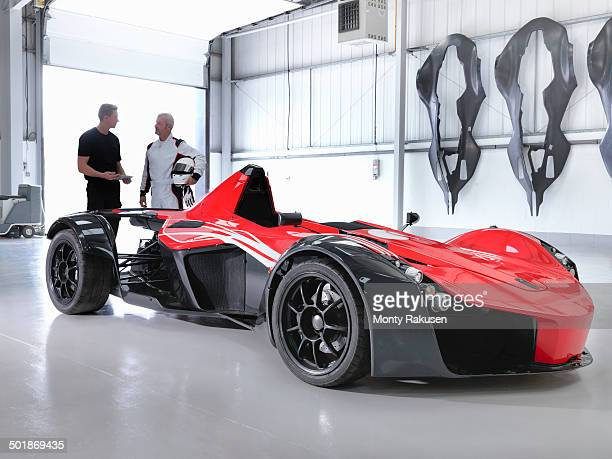 test driver and engineer with supercar in car factory - test drive stock pictures, royalty-free photos & images