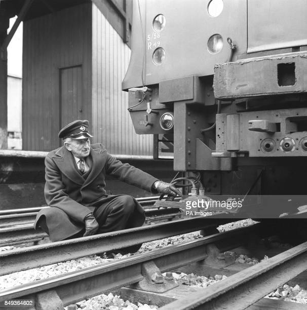 Test driver Jack Sharpley points to pickup coils beneath the front of the train which are part of the 'automatic driving equipment' being tested for...