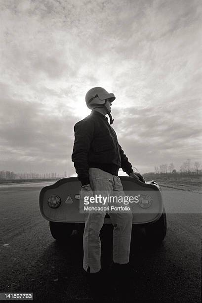 A test driver of the Alfa Romeo Italian car company standing in front of a car in the Balocco trial track Balocco
