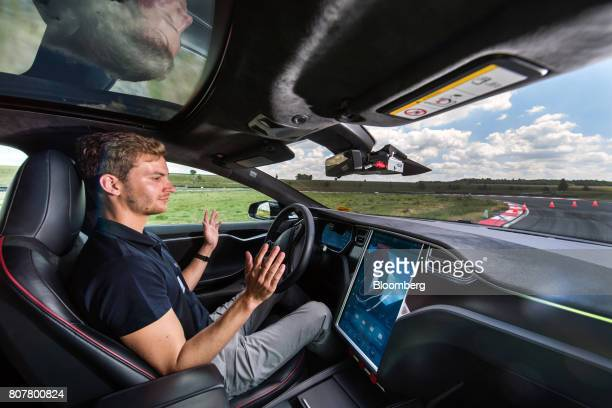 A test driver removes his hands from the steering wheel of a Tesla Motors Inc Model S electric automobile fitted with self driving technology...