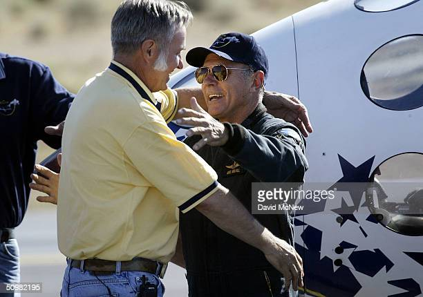 Test pilot Michael Melvill hugs aerospace engineer Burt Rutan after emerging from SpaceShipOne which took him to a height of 62 miles in the first...