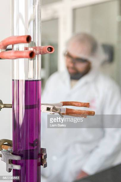 Test tube of purple fluid with worker behind