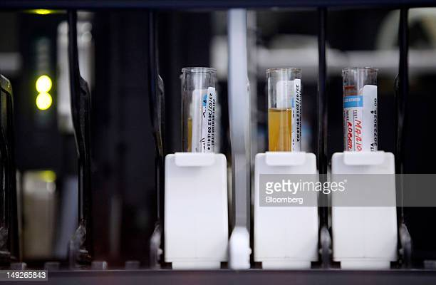 Test tubes hold blood samples as they sit within an Architect ci4100 automated analyzer manufactured by Abbott Laboratories inside the medical...