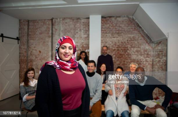 testimonial portrait of a beautiful muslim woman, with diverse creative business team behind her - north african ethnicity stock pictures, royalty-free photos & images