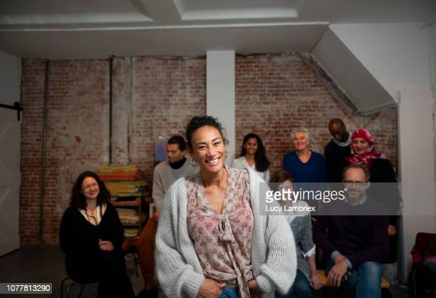 testimonial portrait of a smiling woman, with diverse creative business team behind her - middelgrote groep mensen stockfoto's en -beelden