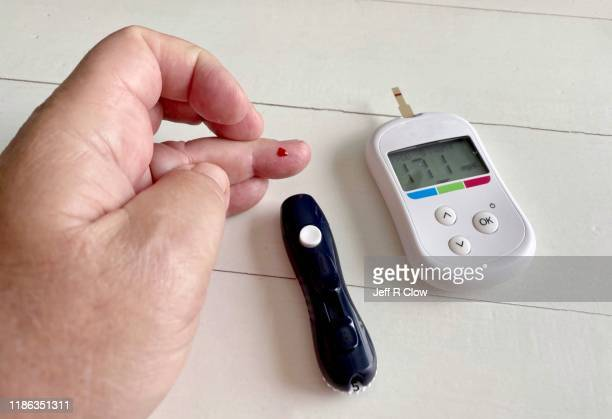 testing a senior adult's blood sugar - glucose stock pictures, royalty-free photos & images